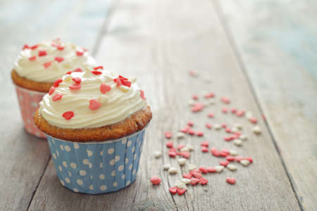 Cupcakes with icing in shape of hearts on wooden background photo
