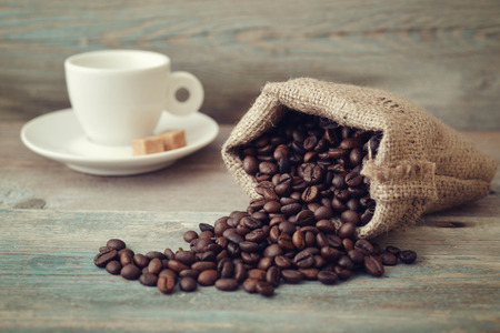 coffee sack: Sack of coffee beans with cup on wooden background closeup Stock Photo