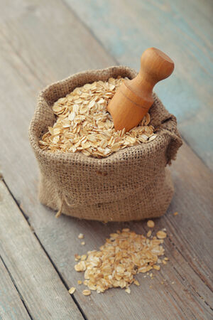 sac: Oat flakes in sac with wooden scoop on wooden background