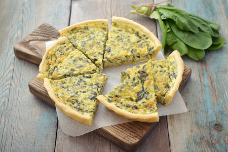 wooden table top view: Traditional french quiche pie with spinach and cheese on wooden background
