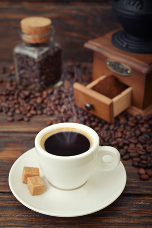Cup of hot espresso with  vintage coffee grinder on wooden background photo
