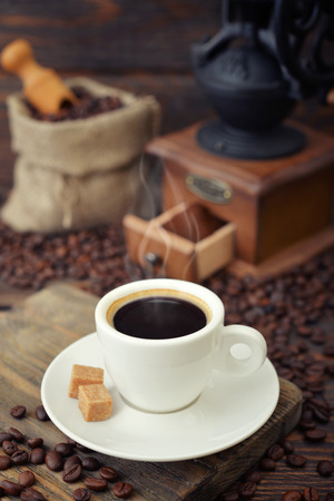 Cup of hot espresso with  vintage coffee grinder on wooden background Stock Photo