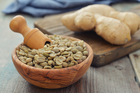 unprocessed: Green coffee beans  in wooden bowl with ginger