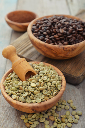 Green and roasted coffee beans  in wooden bowl closeup photo
