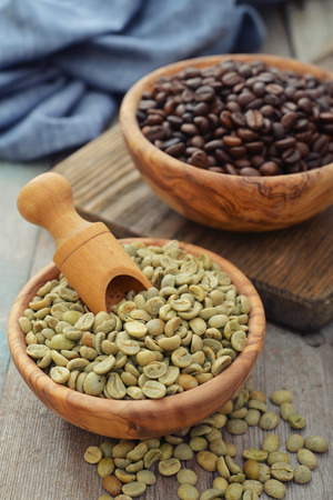unprocessed: Green and roasted coffee beans  in wooden bowl closeup Stock Photo
