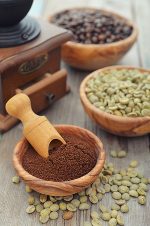 Ground coffee, green and roasted coffee beans  in wooden bowl closeup photo