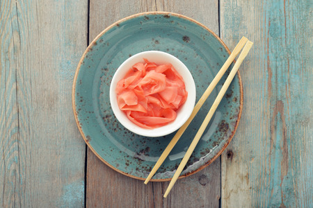 Pickled ginger with wooden chopsticks on plate top view