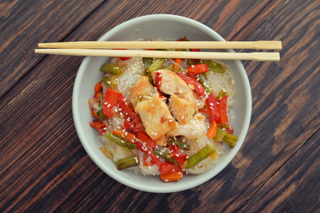 Rice noodles with chicken and vegetables in bowl top view photo