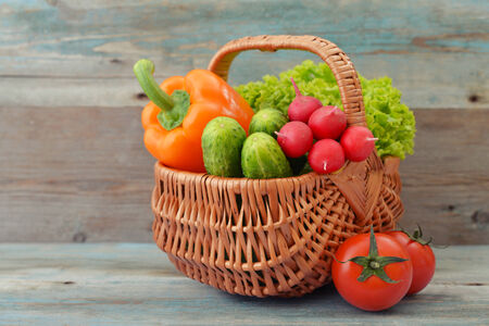 vegetable basket: Organic vegetables in the wicker basket on wooden background Stock Photo
