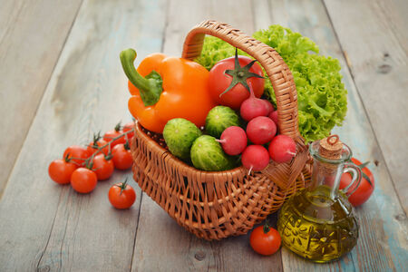 Organic vegetables in the wicker basket on wooden background photo