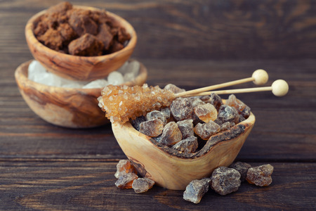 Brown and white sugar in wooden bowl closeup on wooden background photo