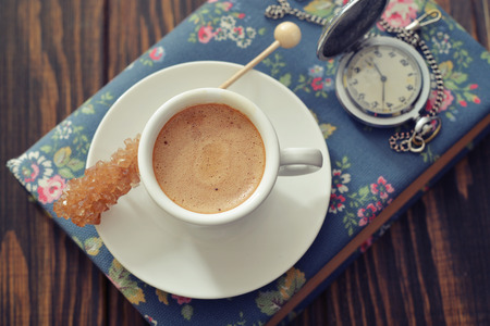 Cup of esspresso with candy sugar on book, top view photo