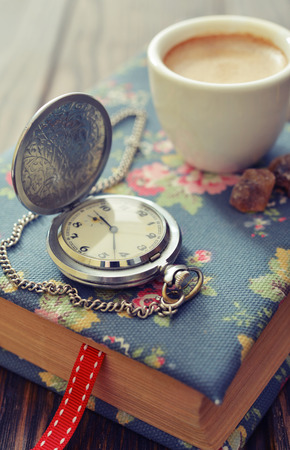 pocket book: Vintage pocket watch with cup of coffee on old book closeup