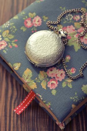 pocket book: Vintage pocket watch on old book closeup