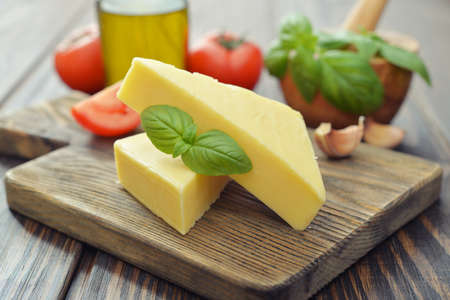 Hard cheese with basil on wooden cutting board photo
