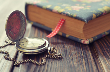 pocket book: Vintage pocket watch with old book closeup Stock Photo