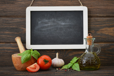 Blackboard with food ingredients on wooden background photo