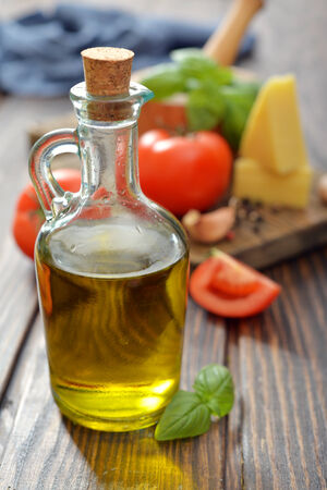 Olive oil  in bottles with tomato, garlic and basil on wooden background photo