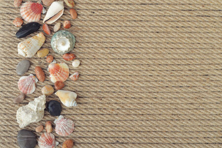 lashing: Sea shells and stones on background of rope closeup Stock Photo