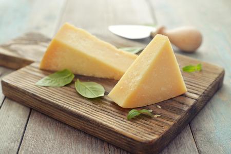 Parmesan Käse auf Schneidebrett mit Basilikum und Messer auf Holzuntergrund Standard-Bild - 28803159