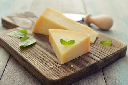 parmesan cheese: Parmesan cheese on cutting board with basil and knife on wooden background