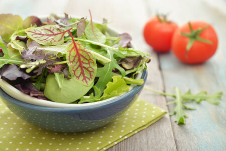 spinach salad: Salad mix with arugula, radicchio and lambs lettuce in bowl on wooden background Stock Photo