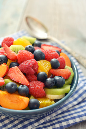 Fruit salad with fresh berries in bowl on wooden background photo