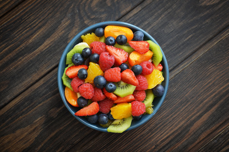 Fruit salad with fresh berries in bowl on wooden background Stock Photo