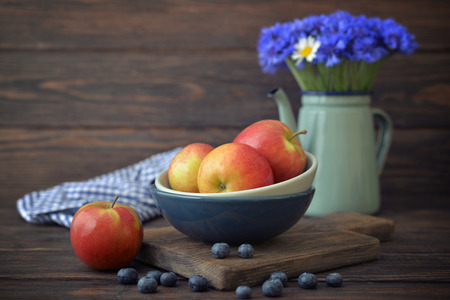 Apples and blueberry in bowl and flowers in  kettle with on wooden background  photo