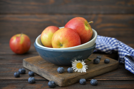 Apples and blueberry in plate on wooden background closeup photo