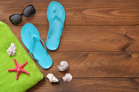 towel beach: Blue Flip-flops with red starfish and towel on wooden background, top view