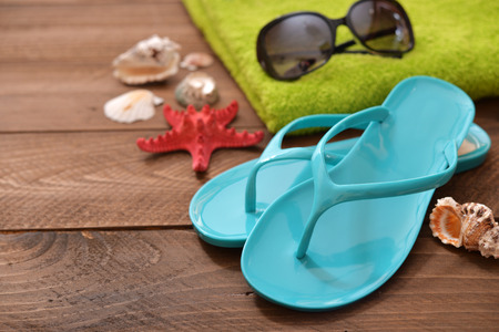 beach towel: Vacation Concept. Blue Flip-flops with red starfish and towel on wooden background