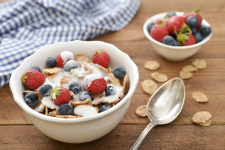 Whole-grain flakes with fresh berries in bowl and yogurt on wooden background photo