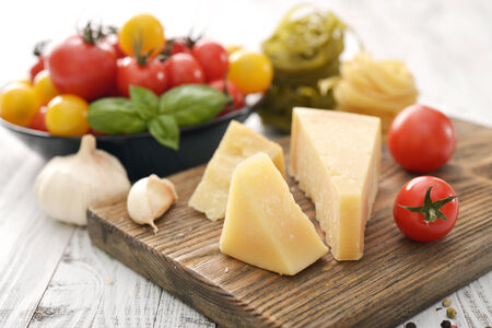 wedge: Parmesan cheese on cutting board with basil and tomato on wooden background