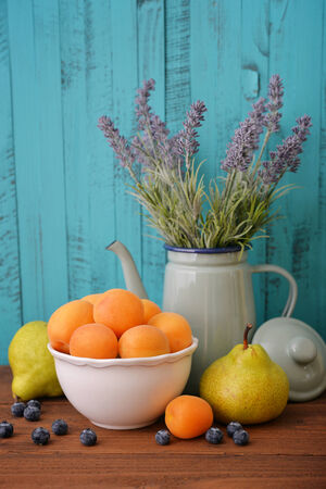 colorful still life: Apricots in bowl with fresh pear and blueberry on wooden background