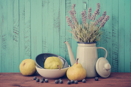 colorful still life: Pear in bowl with fresh blueberry and lavender flowers on wooden background