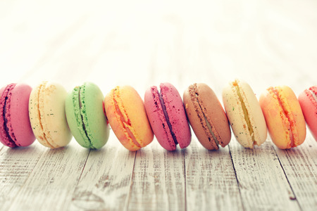 kinds: Different kinds of macaroons in stack on light wooden background