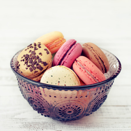 packaged: Different kinds of macaroons in glass vase on light wooden background