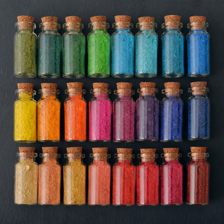 Bottles with colored powder dyes on a black background Stock Photo