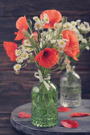 vintage bottle: Wildflowers and poppies flowers in vintage bottle  on wooden background Stock Photo