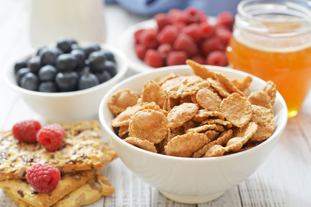 corn flakes: Whole-grain flakes in bowl with fresh berries on light background