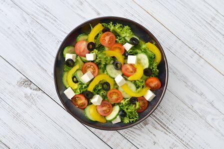 feta cheese: Fresh vegetable salad with cheese feta on plate closeup