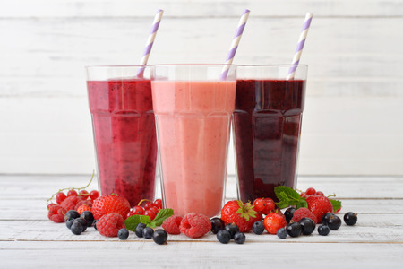 Three glasses of smoothies with different berries on wooden background photo