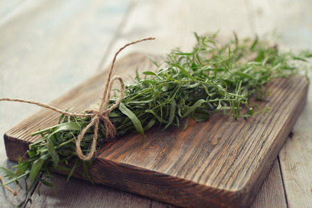 tarragon: Fresh tarragon on wooden cutting board closeup