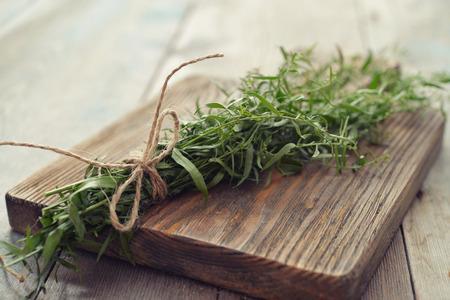 tarragon: Fresh tarragon on wooden cutting board closeup