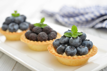 blackberries: Delicious mini tart with fresh blackberries and blueberries on wooden background Stock Photo