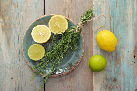 tarragon: Fresh tarragon with lemon and lime on wooden background