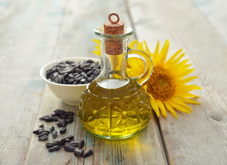 Zonnebloemolie in flessen met zaden en bloemen op houten achtergrond Stockfoto