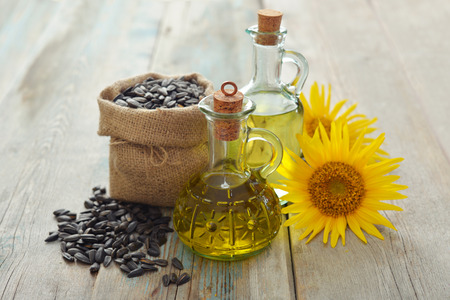 sunflowerseed: Sunflower oil in bottles with  seeds and flower on wooden background Stock Photo
