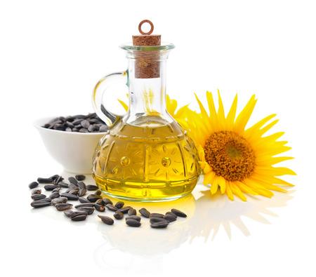 Zonnebloemolie in fles met zaden en bloemen op een witte achtergrond Stockfoto